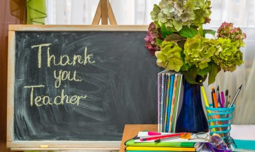 Teacher  Day. Hydrangea flowers and copybooks on the teacher d